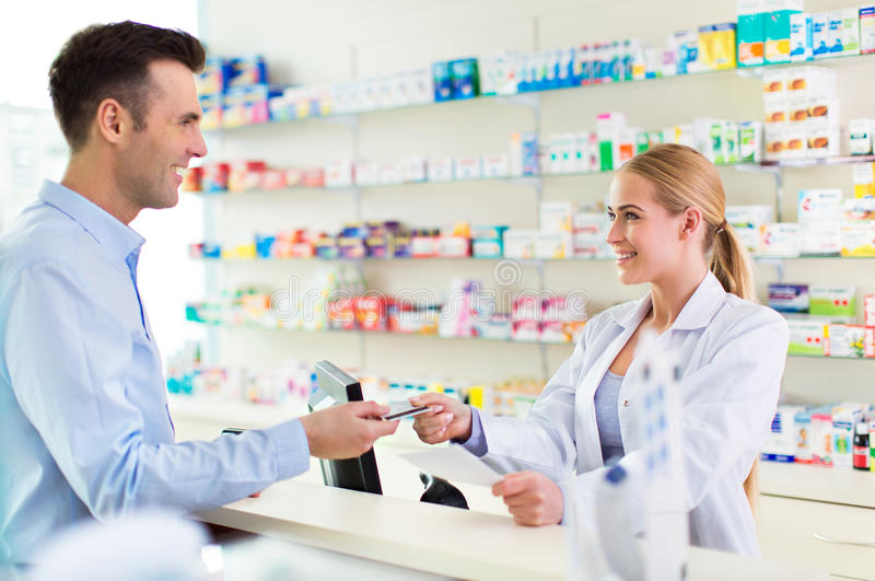 Apotekare och klient på apotek arkivfoton