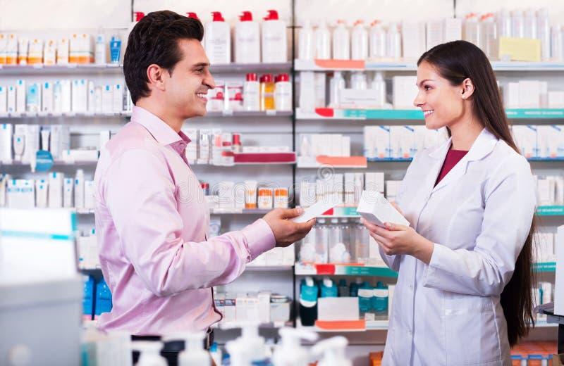 Apotekare och konsulterande man i apotek arkivfoton