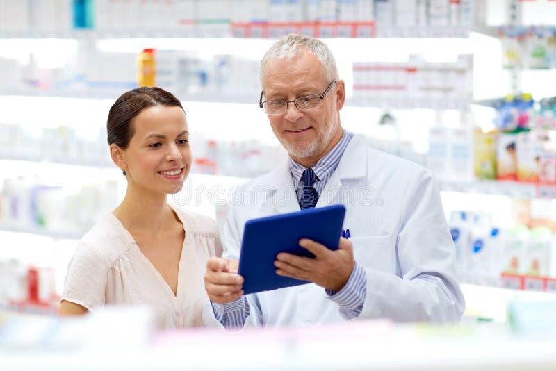 Apotekare och kund med minnestavlaPC på apotek royaltyfria bilder