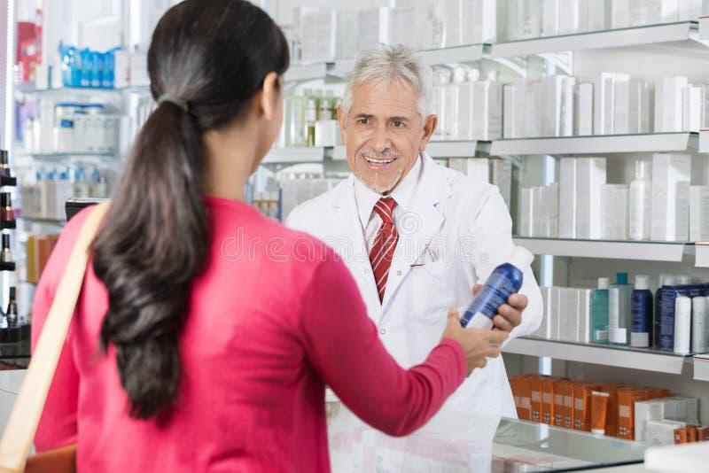 Apotekare Selling Deodorant Bottle till kvinnan royaltyfria bilder