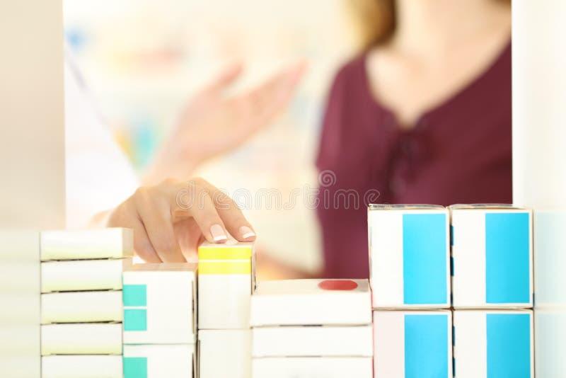 Apotekare som deltar i en kund i ett apotek arkivfoto