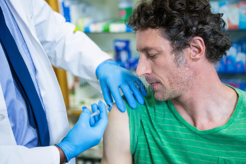 Apotekare som ger injektionen till patienten royaltyfri fotografi