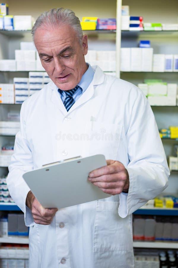 Apotekare som läser ett recept arkivfoto