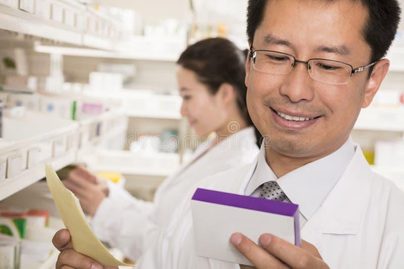 Apotekare som ner ser, och undersökande receptläkarbehandling i ett apotek arkivbild