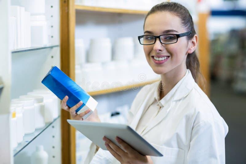 Apotekare som rymmer den digitala minnestavlan, medan kontrollera medicin i apotek royaltyfri bild