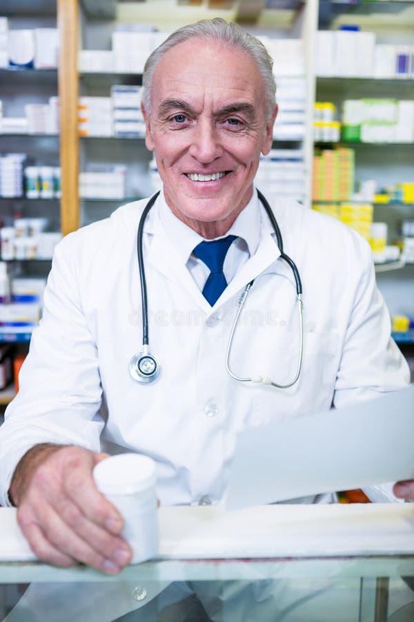 Apotekare som rymmer ett recept och en medicin royaltyfri fotografi