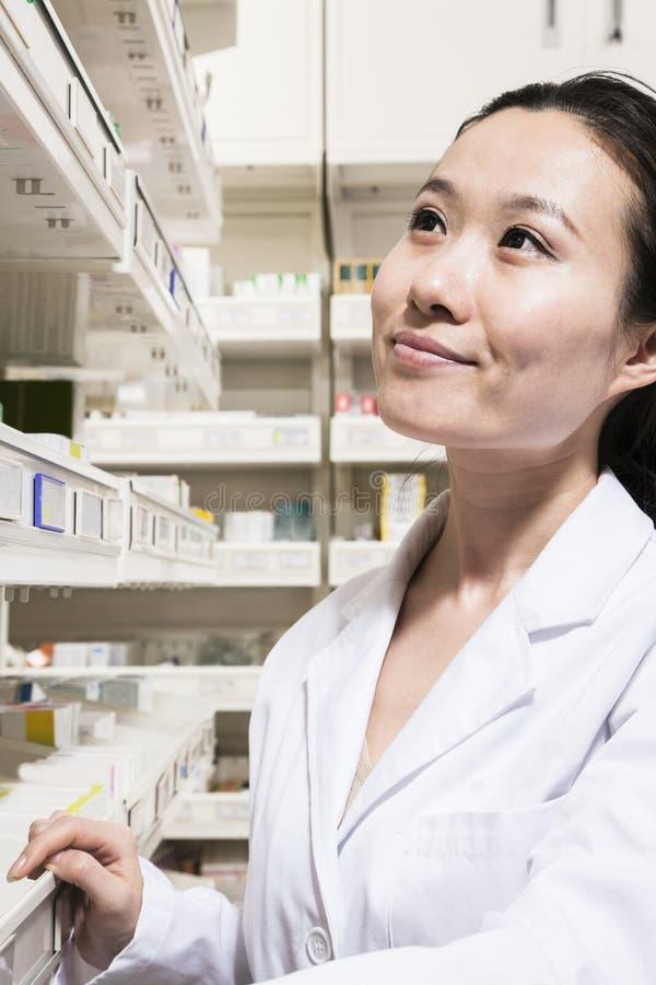 Apotekare som söker efter läkarbehandlingen på en hylla i ett apotek arkivfoto