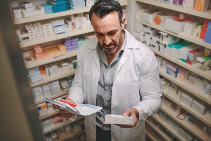 Apotekare som söker efter några läkarbehandlingar i apotek arkivbilder