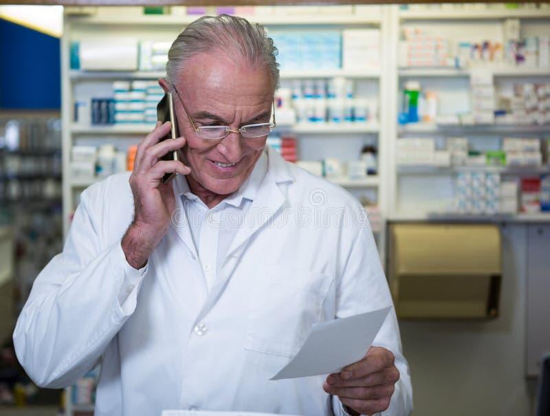 Apotekare som talar på mobiltelefonen, medan kontrollera receptet arkivfoto