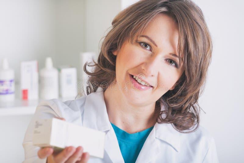 Apotekare som visar en medicin i apoteket arkivfoto