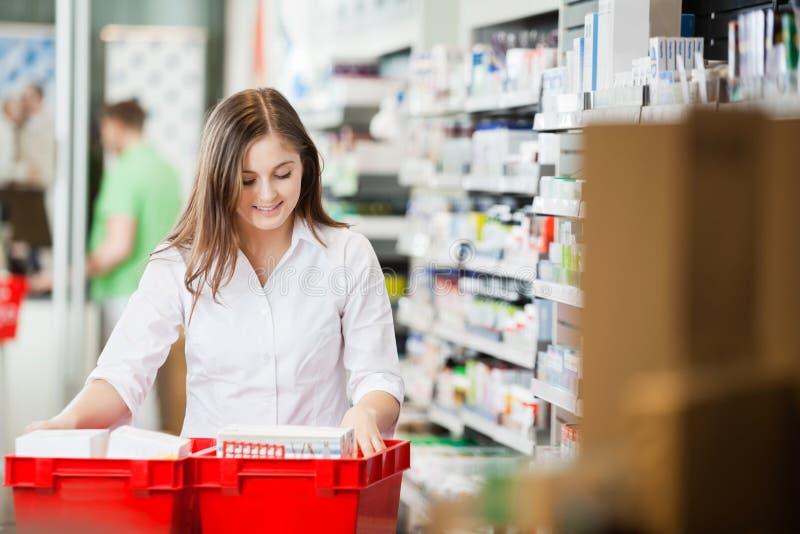 Apotekare Stocking Shelves i apotek royaltyfria foton