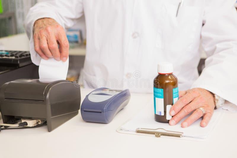 Apotekareinnehavkrus av medicin och kvittot royaltyfri foto