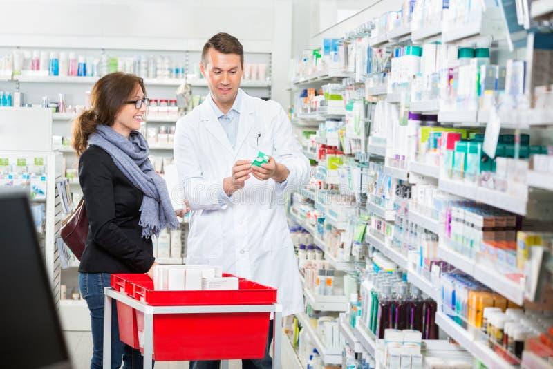 ApotekareShowing Medicine To kvinnlig kund in royaltyfria foton