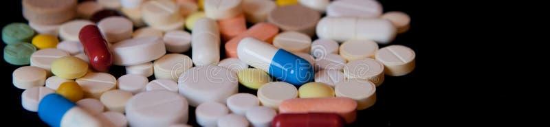 Apotekbakgrund på en mörk tabell Svävningpreventivpillerar Minnestavlor på en mörk bakgrund som som ner faller pills Medicin och  fotografering för bildbyråer
