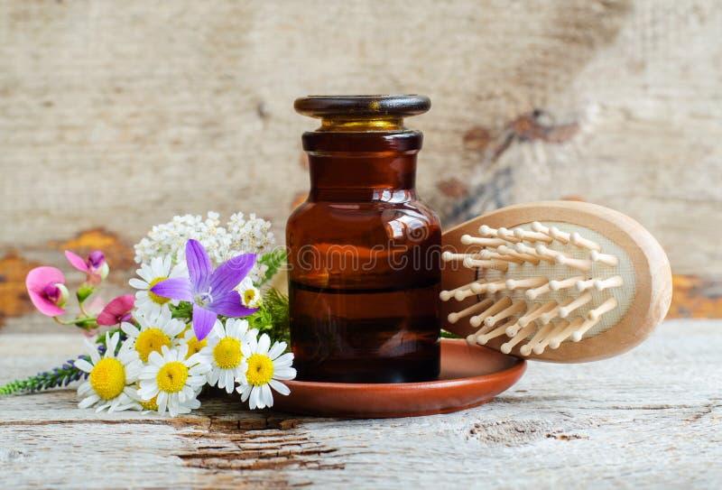 Apotekflaska, lösa blommor och trähårborste Nödvändig olja för växt- tinktur, avkok, extrakt gammalt tr? f?r bakgrund royaltyfri foto