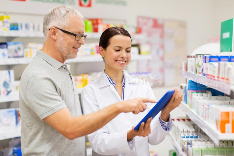 Apothecary and customer with tablet pc at pharmacy stock images