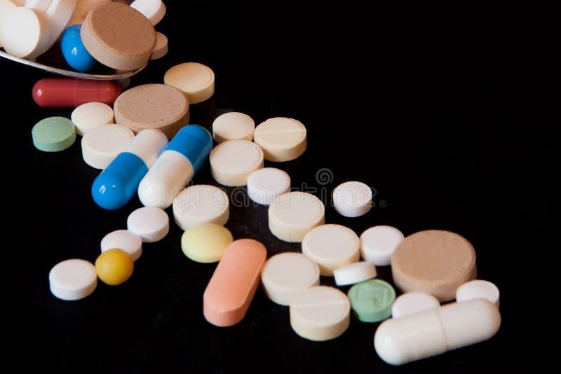 Apotheekachtergrond op een zwarte lijst Tabletten met een lepel Pillen Geneeskunde en gezond Sluit omhoog van capsules Verschille stock foto's