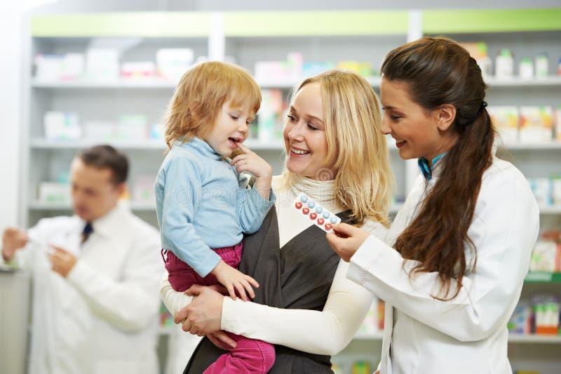 Apothekechemiker, -mutter und -kind im Drugstore stockbilder