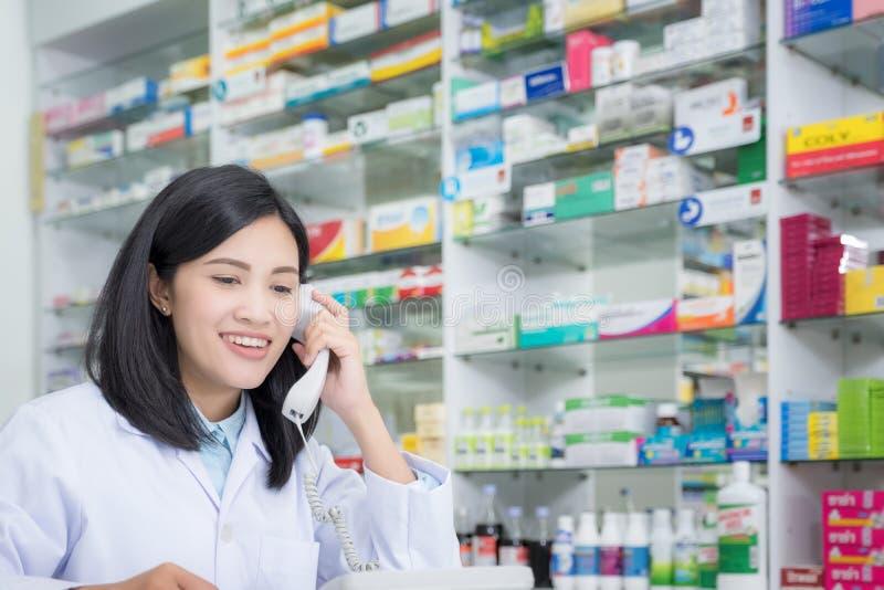 Apothekenarbeitskraft, die telefonisch, attraktive junge l?chelnde Frau am Schreibtisch mit Telefon mit Ohr spricht lizenzfreie stockfotos