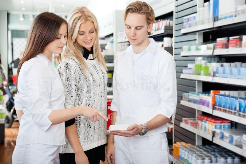 Apotheker Assisting Female Shopper stock afbeeldingen