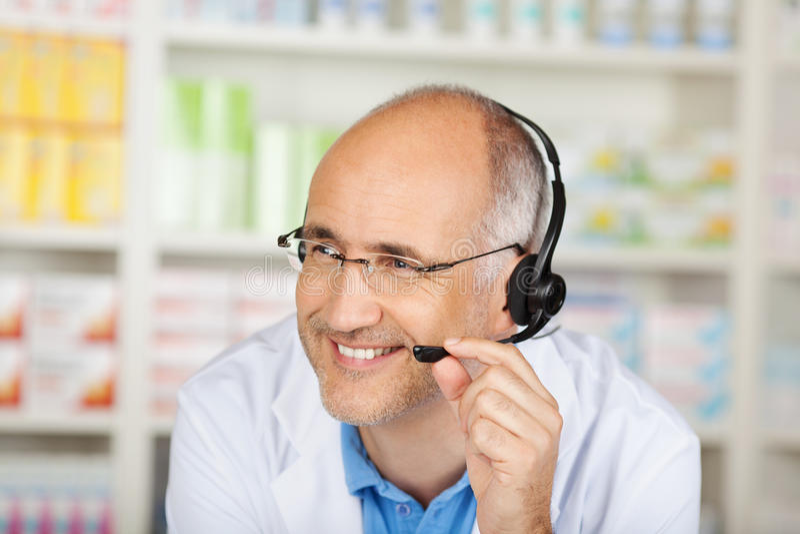 Apotheker Conversing On Headset in der Apotheke lizenzfreie stockfotos