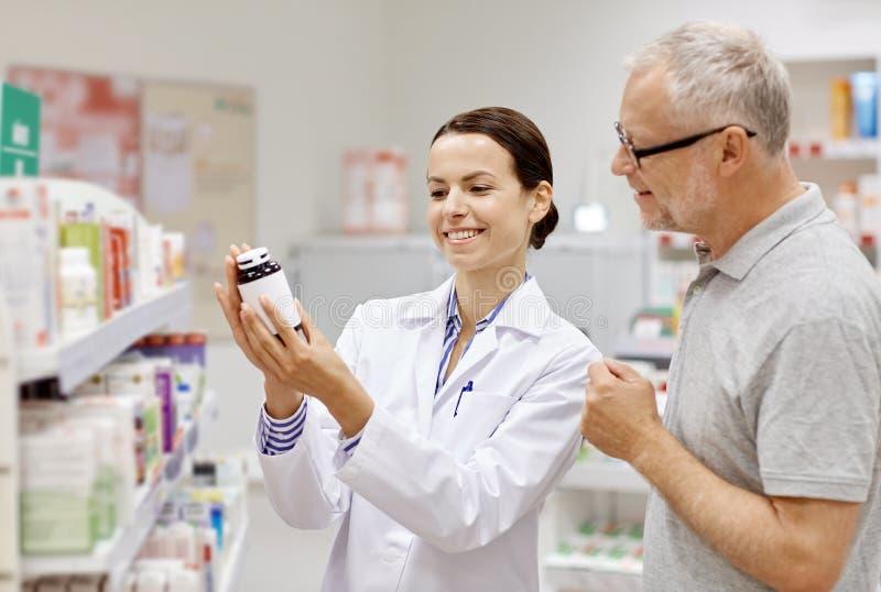 Apotheker, der dem älteren Mann Droge an der Apotheke zeigt lizenzfreie stockfotos