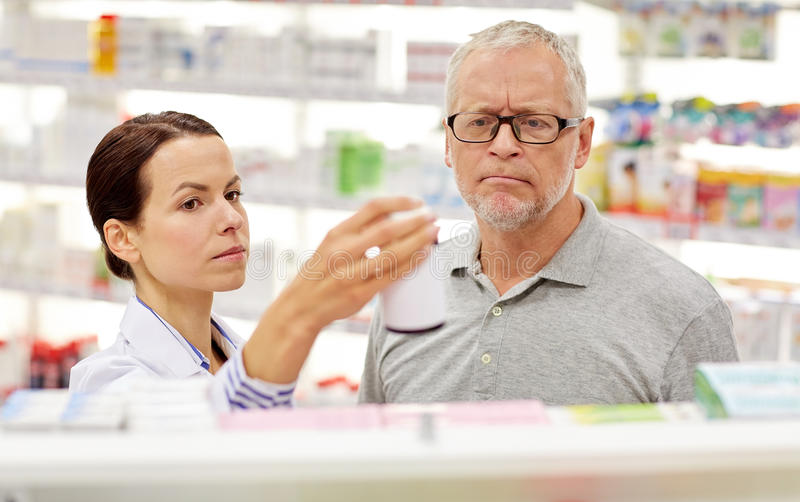 Apotheker, der dem älteren Mann Droge an der Apotheke zeigt stockbilder