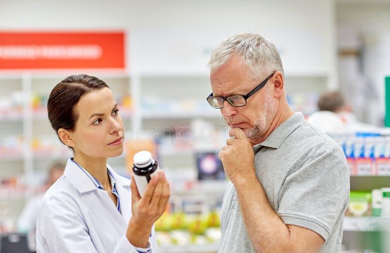 Apotheker, der dem älteren Mann Droge an der Apotheke zeigt lizenzfreie stockfotografie