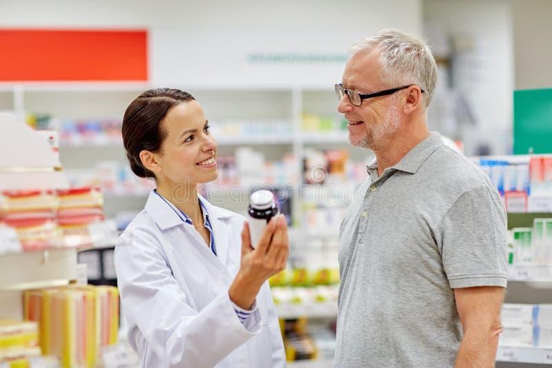 Apotheker, der dem älteren Mann Droge an der Apotheke zeigt stockfoto