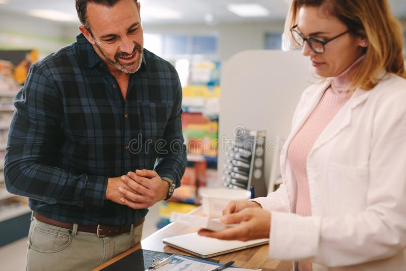 Apotheker, der dem Kunden Rat über einer Medizin gibt stockfoto