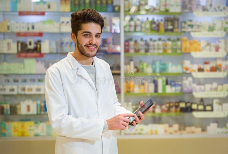 Apotheker, der digitale Tablette in der Apotheke hält stockfotos