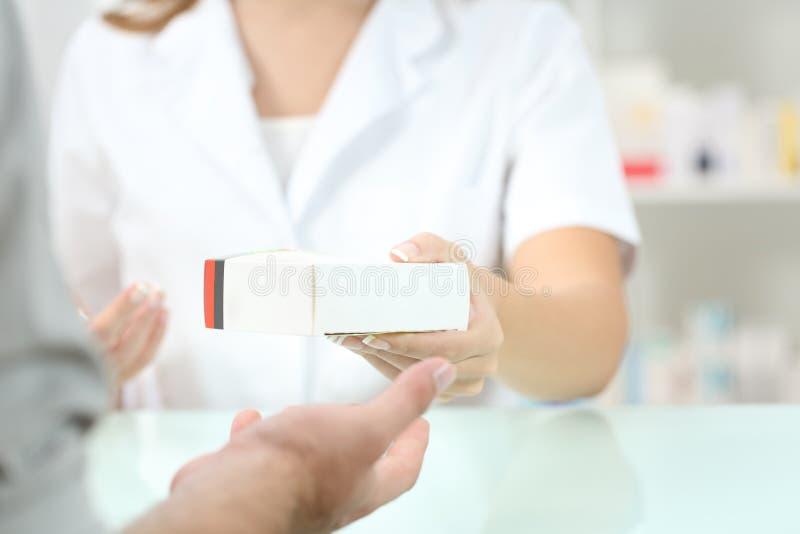 Apotheker, der einem Kunden einen Medikament gibt lizenzfreies stockfoto
