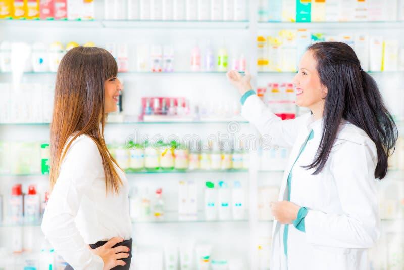 Apotheker, der medizinische Droge Käufer in der Apotheke vorschlägt stockfotos