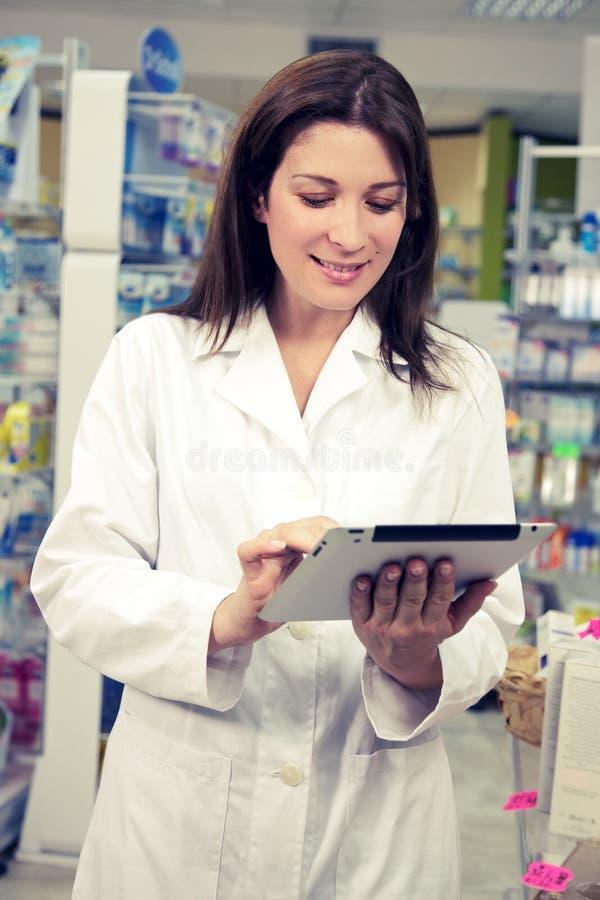 Apotheker, der mit Tablette in der Apotheke arbeitet lizenzfreies stockfoto
