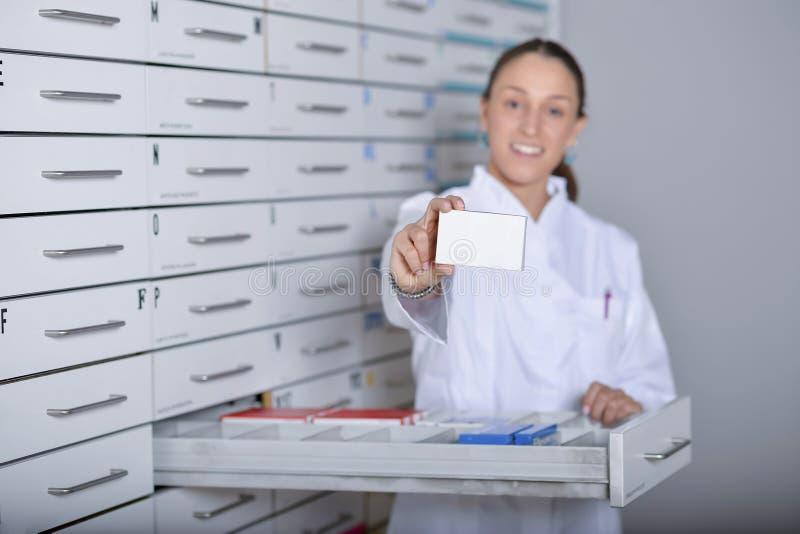 Apotheker, der weißen leeren Medizinkasten mit Apothekenspeicher zeigt lizenzfreies stockfoto