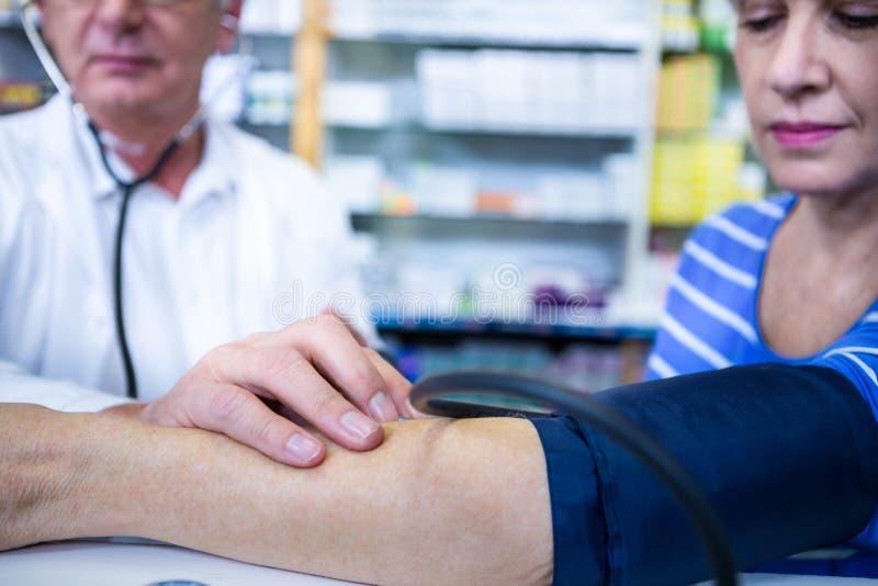 Apotheker die bloeddruk van klant controleren royalty-vrije stock afbeelding