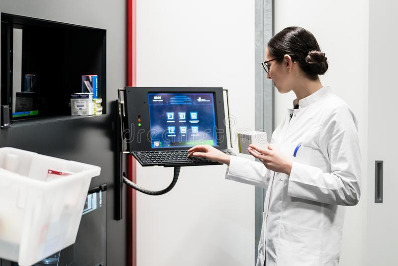 Apotheker die een computer met behulp van terwijl het leiden van de drugvoorraad stock afbeelding