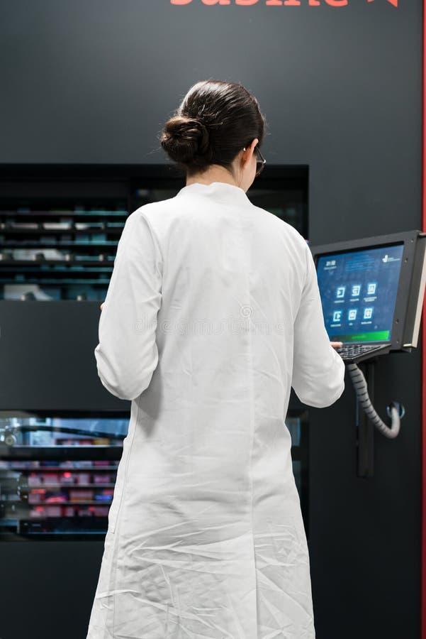 Apotheker die een computer met behulp van terwijl het leiden van de drugvoorraad in apotheek royalty-vrije stock fotografie