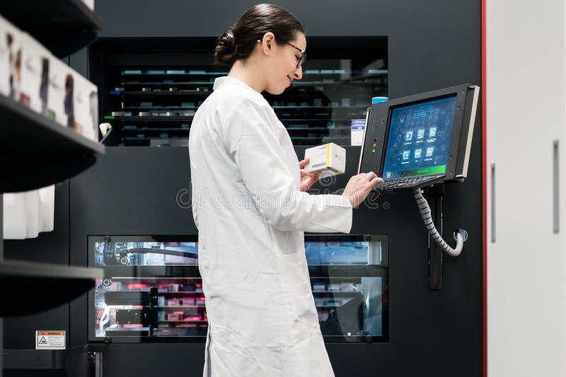 Apotheker die een computer met behulp van terwijl het leiden van de drugvoorraad in pha stock fotografie