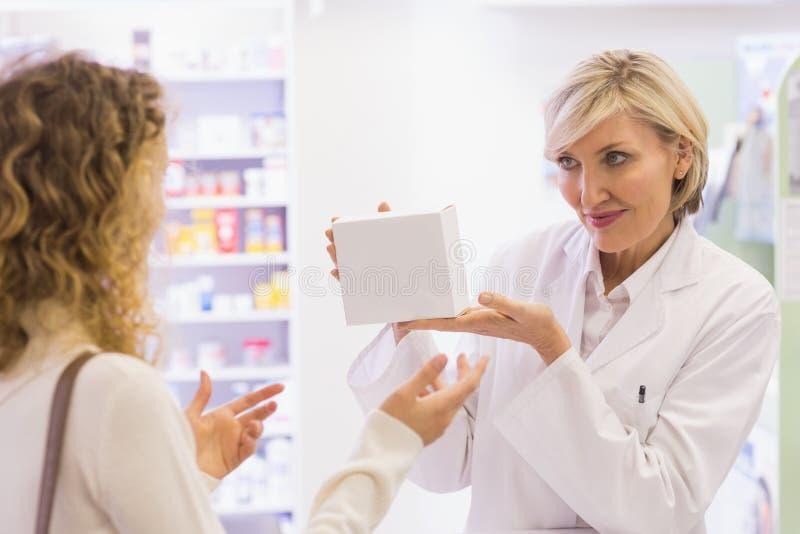 Apotheker die een fles van drugs houden die aan klant spreken stock foto