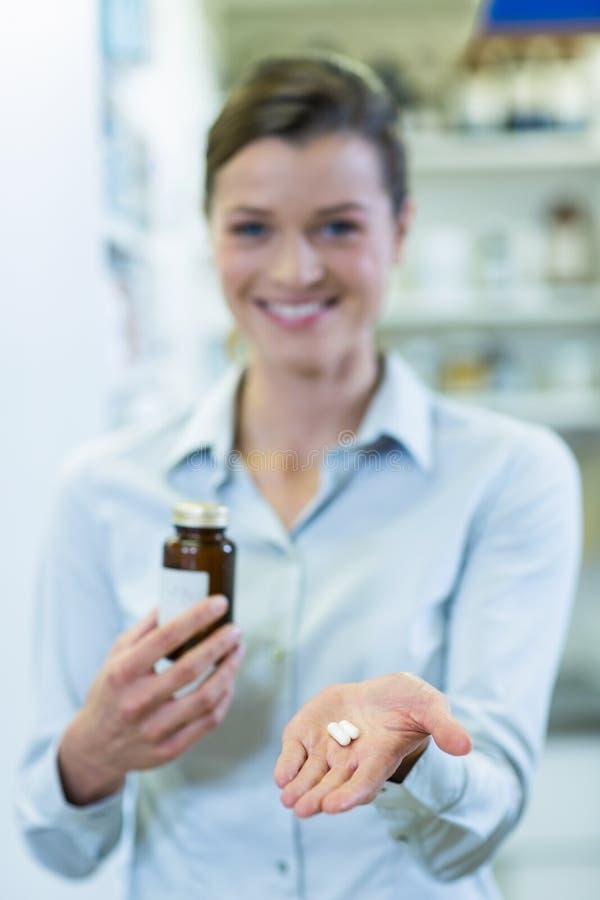 Apotheker die een geneeskundefles en pillen in apotheek tonen stock afbeelding