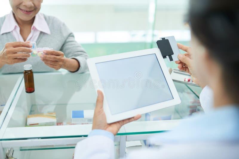 Apotheker die kaartlezer met behulp van stock afbeelding