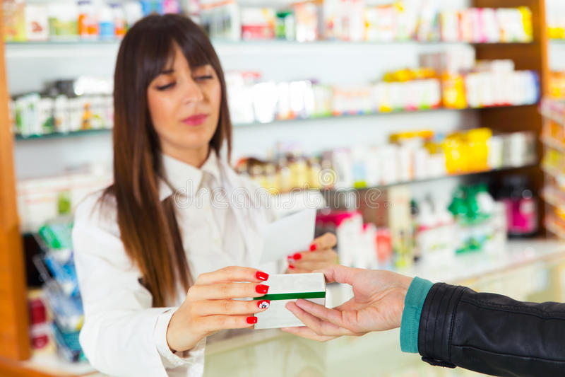 Apotheker die medische drug voorstellen aan koper in apotheek stock fotografie