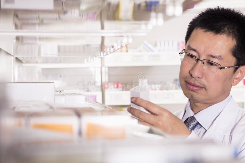 Apotheker die neer en voorschriftmedicijn in een apotheek nemen onderzoeken royalty-vrije stock fotografie