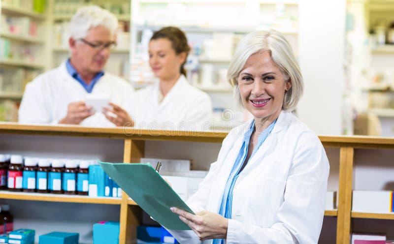 Apotheker die op klembord in apotheek schrijven stock foto