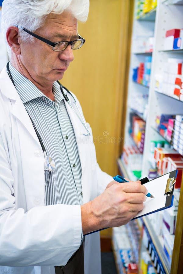 Apotheker die op klembord in apotheek schrijven stock foto's