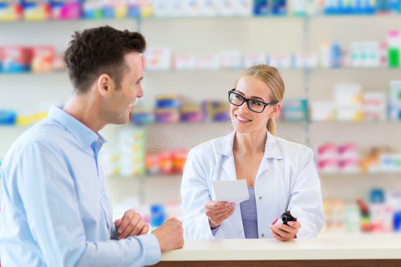 Apotheker en cliënt bij apotheek stock afbeeldingen