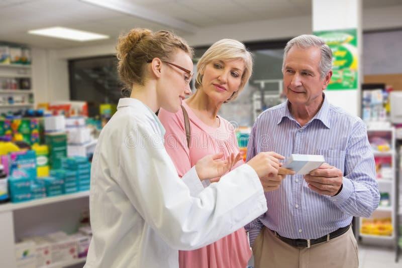 Apotheker en haar klanten die over medicijn spreken royalty-vrije stock afbeelding