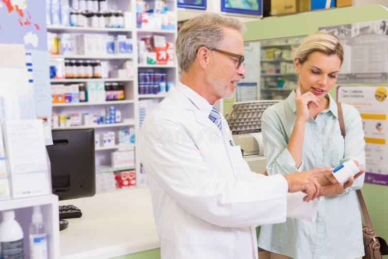 Apotheker en klant die over medicijn spreken royalty-vrije stock foto's