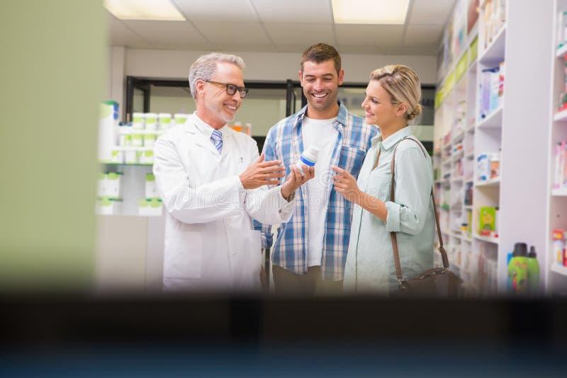 Apotheker en klanten die over medicijn spreken stock afbeeldingen
